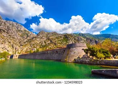 Large historical medieval stone wall in front of a moat with green water on the backdrop of the picturesque mountains on a sunny day. Kotor Venetian fortifications, Kampana Tower Old Town, Montenegro.