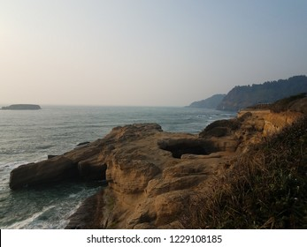 large hole in cliff at Oregon coast with ocean and waves