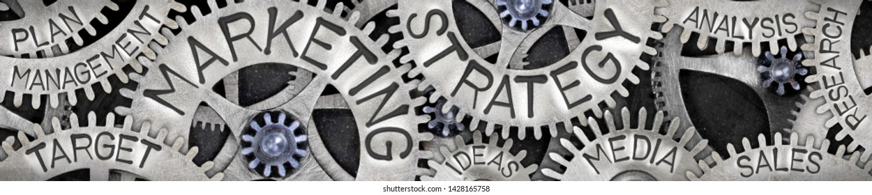 Large horizontal group of tooth wheels with Marketing Strategy concept related words imprinted on metal surface