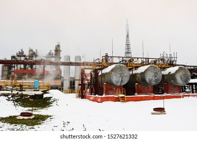 Large horizontal shell-and-tube tanks heat exchangers with liquid at an industrial petroleum refining petrochemical chemical plant in the snow in winter.