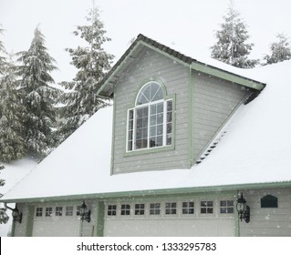 A large house covered in snow including a dormer window and snow on the roof.