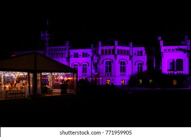 Large house and white banquet wedding tent at night