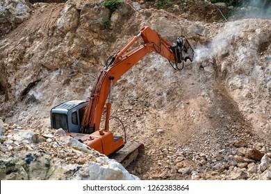 Large hydraulic Jackhammer working on smashing rock.