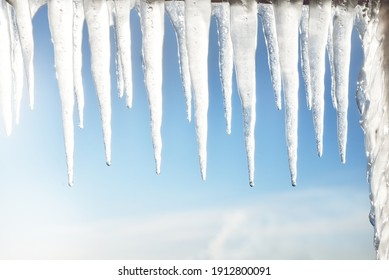 Large icicles close-up. Clear blue sky. Concept winter landscape. Midday sun. Seasons, ecology, environment, climate change, global warming, anomaly, nature. Panoramic view, copy space