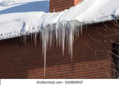 Large icicles hanging from the roof of a brick house