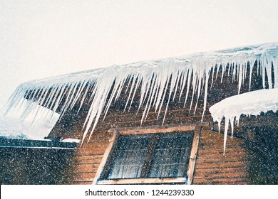 Large icicles on the roof of a wooden house on a snowy day