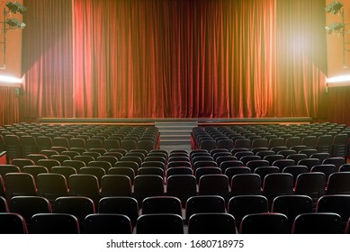 Large illuminated theatre hall with empty seats viewed from the rear looking towards the stage with its closed red curtain in a performing arts concept