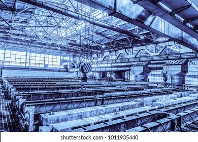 Large industrial bath for galvanizing steel metal products. Hooks of overhead cranes. Unified standard typical span prefabricated of a steel frame production building. Background in blue tone.