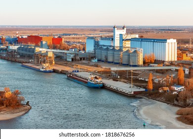 The large industrial building of a grain elevator placed on the bank of a river near a cargo berth for loading grain onto dry cargo ships. Export wheat trade.