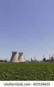 large Industrial chimneys at Refineries in Israel Haifa against green fields