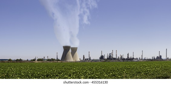 large industrial chimneys with white smoke at refineries against green fields i