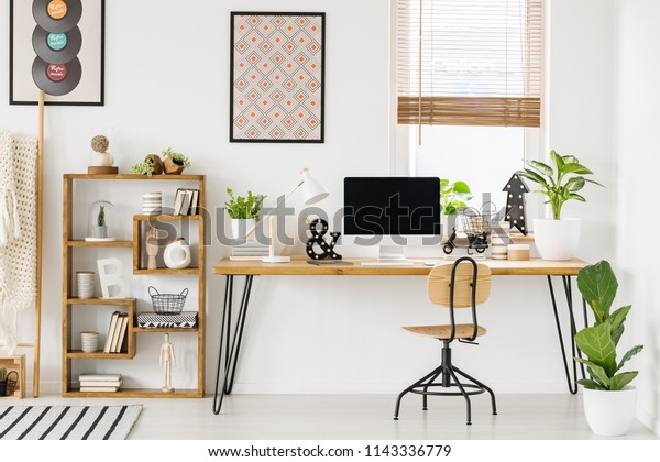 Large industrial desk with a computer by a window, a wooden bookcase and posters on a white wall in a stylish, scandi home office interior