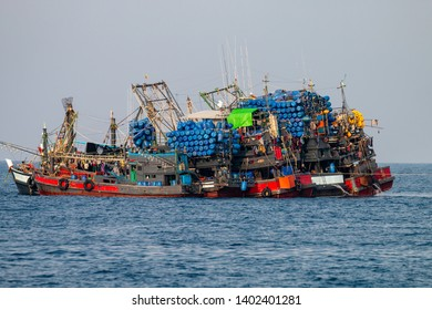 Large industrial fishing trawlers operating together in a tropical ocean