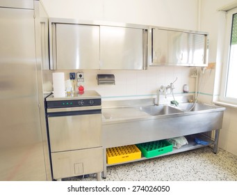 large industrial kitchen with refrigerator, dishwasher and sink all stainless steel