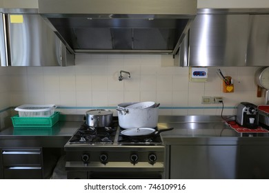 large industrial kitchen with stainless steel cookers and large suction hood