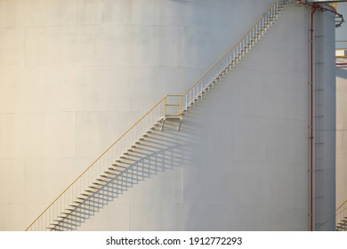 large Industrial tanks for petrol and oil with blue sky.Fuel tanks at the tank farm. metal stairs on the side of an industrial oil container.Staircase on big fuel tank