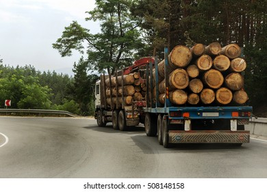 Large industrial timber trailer transports freshly sawn logs on the mountain road car. Procurement and Logistics business softwood industrial timber