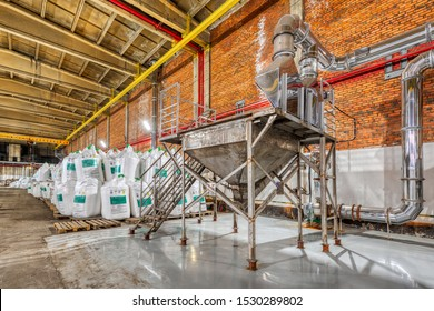 Large industrial warehouse of chemicals. Large white bags filled with powder are arranged in long rows.