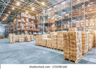Grosses Industriehaus mit hohen Racks. Im Vordergrund sind viele Kartons. Überlastete Lagergebäude.