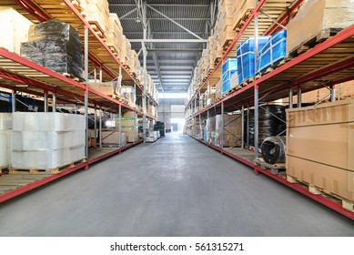 Large industrial warehouse. Long shelves with a variety of boxes and containers.