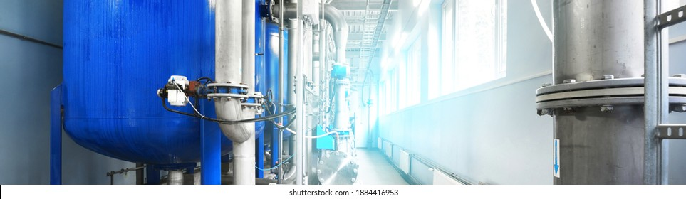 Large industrial water treatment and boiler room. Shiny steel metal pipes, blue pumps, valves. Industry, technology, special equipment, chemistry, environment, heating, work safety. Panoramic view