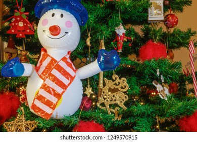 Large inflatable snowman on a Christmas tree. Air blown seasonal figure before an illuminated artificial Christmas tree with lights and colorful decorations.