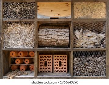 Grosses Insektenhotel mit verschiedenen Materialien in neun Bereichen