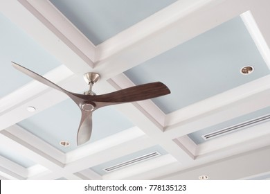 A Large Interior Fan on a Blue Coffered Ceiling