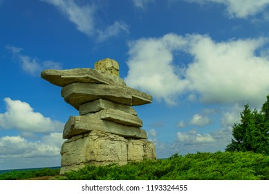 Large inukshuk on a summer day at Sunset Point Beach in Collingwood Ontario on Georgian Bay