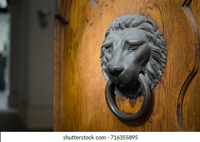 Large iron Lion head doorknocker on a wooden door