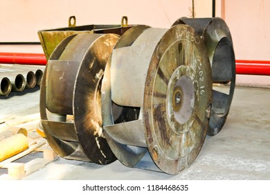 A large iron metal round wheel with louvers to pump water into the pump. Spare part of the transfer pump.