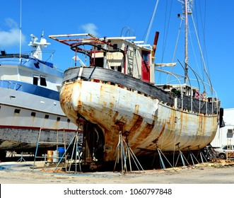 A large iron rusting ship is in dry dock for refurbishing.