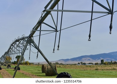 Large irrigation equipment in hay field.