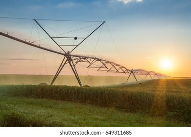 Large irrigation system spraying water in a green wheat field