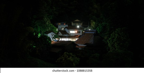 Large Japanese house in the woods with lights on at night