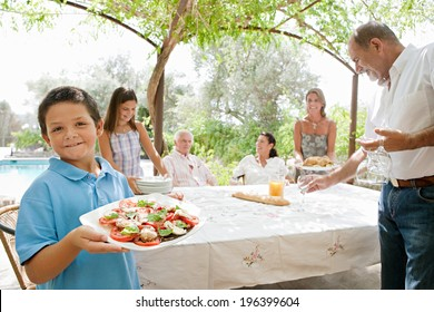 Large joyful family preparing a table outdoors together, placing plates, glasses and healthy food during a sunny holiday day in a vacation villa home garden, outdoors. Teamwork and eating lifestyle.