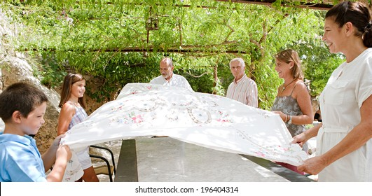 Large joyful family setting a food table together outdoors and coordinating placing a table cloth on during a sunny summer holiday day in a vacation home garden, outdoors. Teamwork and lifestyle.