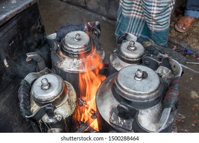 Large kettles brew tea and coffee on an open fire in a street market in an Asian city.