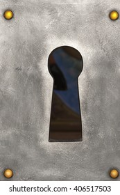 large keyhole in the metal plate with golden nails, closeup