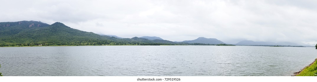 A large lake surrounded by misty hills covered with lush green forests amidst the backdrop of a cloudy sky