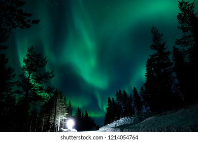 Large lamp illuminating the countryside for tourists to observe the spectacular aurora borealis. Colorful night sky appearing above snowy landscape in Finland. Breathtaking vivid northern lights.