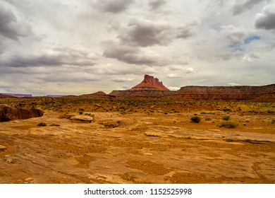 A large land formation stands high above the desert floor. Rock ledges surround the deep abyss to the left, a scene on the way to Millard Canyon in the remote Maze are of Canyonlands NP in Utah.