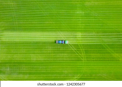 Large Lawn mower cutting green grass in a large flat field - Top down aerial image.
