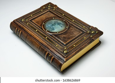 Large leather book with metal frame and the moon picture below thick aged glass.