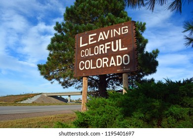Large Leaving Colorful Colorado Wooden Roadside Highway Sign on a Sunny Day