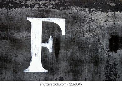A large letter F painted on the side of an old train car