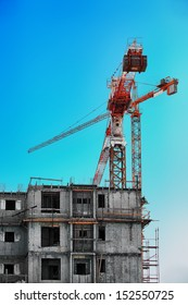 a large lifting crane at the building site near a building under construction