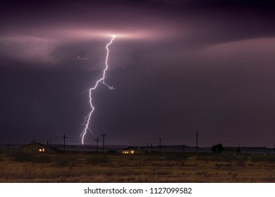 A large lightning strike at dusk in an open plain framed against a deep, dark orange sunset and stormy skies.