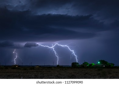 A large lightning strike at night in a rural area of Roswell, New Mexico framed against stormy skies.