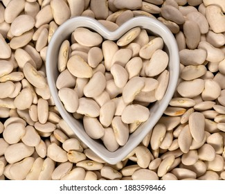Large lima beans in a heart shaped bowl background and texture. Top view.